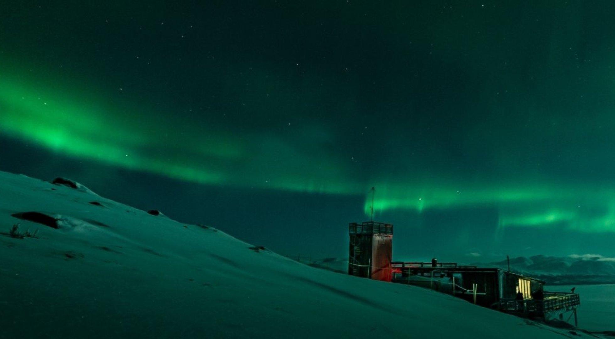 ett grönt norrsken som sverper fram över natthimlen ovan Abisko