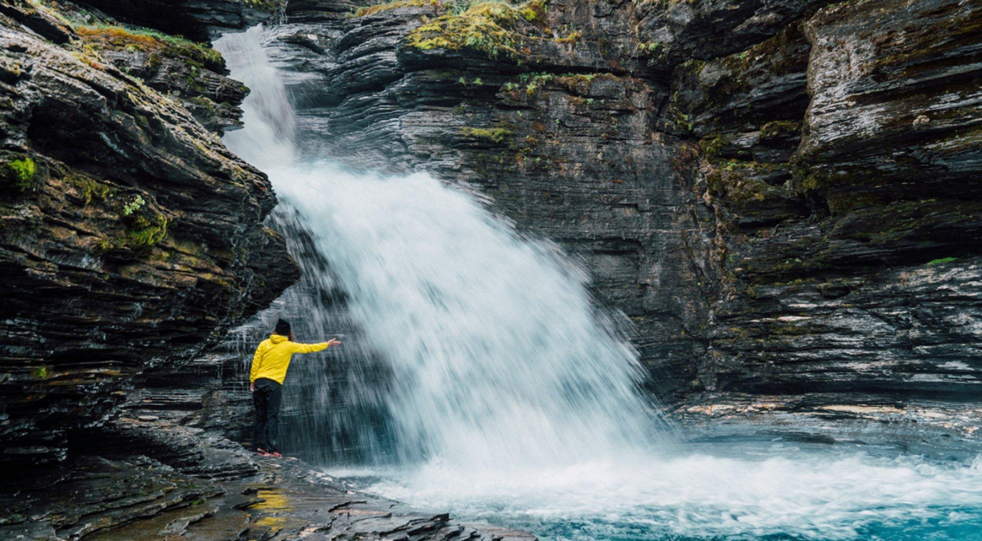Kvinna som sträcker armarna mot ett vattenfall